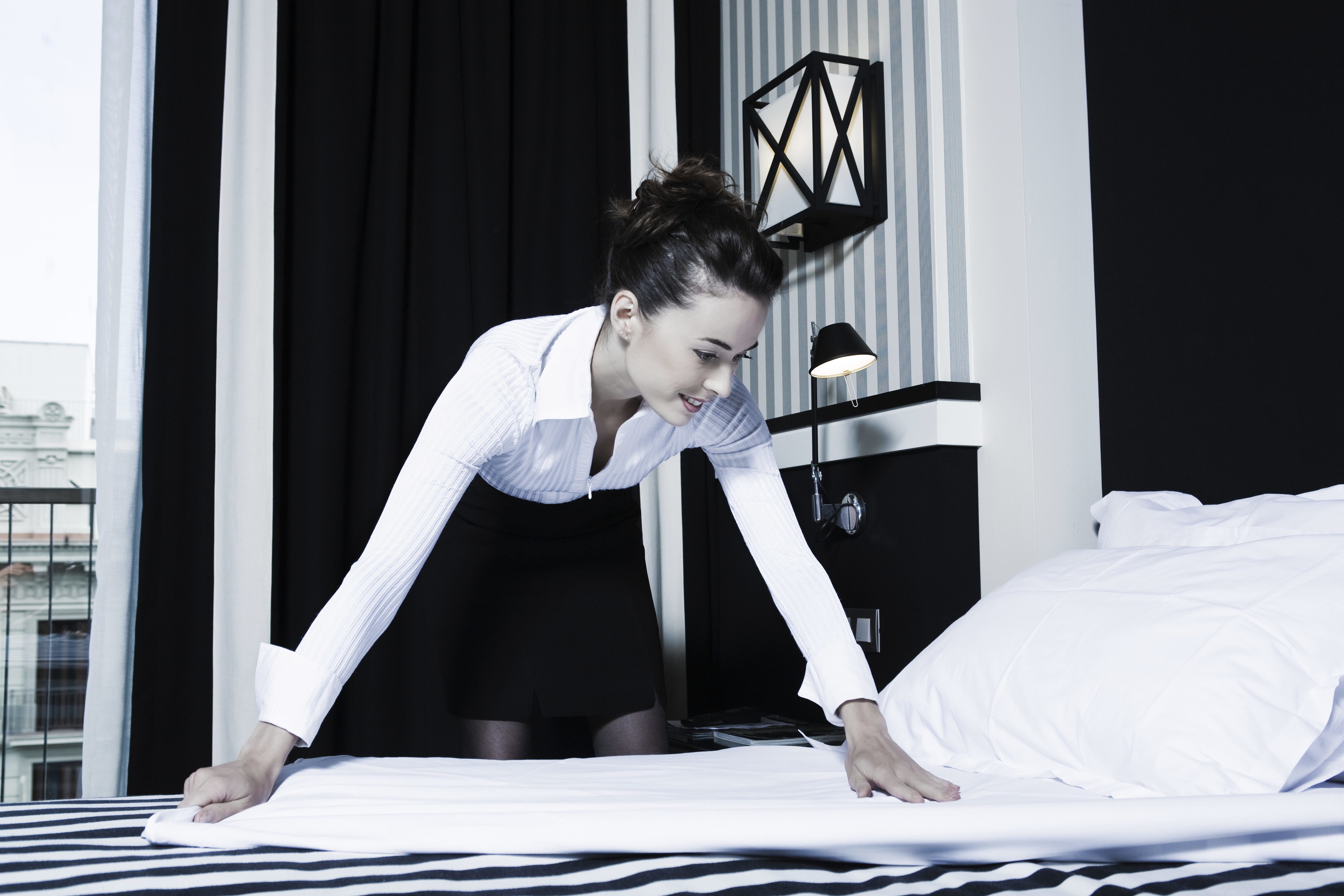 hotel housekeeper making the bed